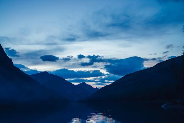 夕暮れの素晴らしい青いシルエット山。夜明けの空は山の湖に反映されます。素晴らしい大気高地の風景。明るいミステリーと湖の水の美しい波紋。風光明媚な山の風景