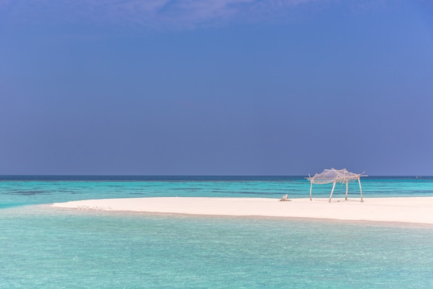 Amazing blue water in a desert island in a blue sky day with a little wood hut