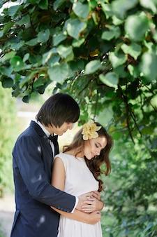 緑の葉の背景、結婚式の写真、美しいカップル、結婚式の日、肖像画で互いに近くに立っている長い巻き毛と花婿を持つ素晴らしい花嫁。