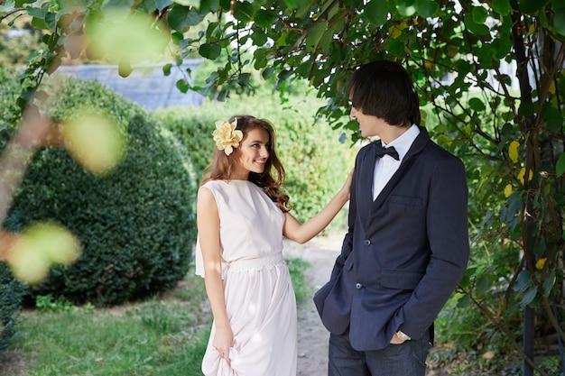 緑の葉の背景、結婚式の写真、美しいカップル、結婚式の日に互いに近くに立っている長い巻き毛と花婿を持つ素晴らしい花嫁。