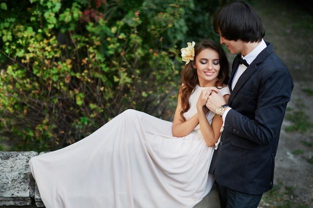 긴 곱슬 머리와 신랑 녹색 잎 배경, 웨딩 사진, 아름 다운 커플에서 서로 가까이 서있는 놀라운 신부.