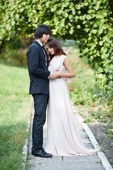 Amazing bride with long curly hair and bridegroom standing close to each other at green leaves, wedding photo, beautiful couple, wedding day.