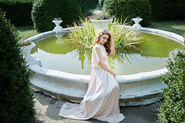 Amazing bride with long curly hair in wedding dress sitting near fountain at park, wedding photo, portrait.