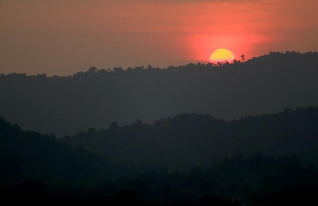 山脈のシルエットに沈む夕日