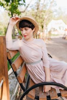 Incredibile ragazza bruna comodamente sistemata su una panca di legno e pensando a qualcosa