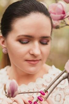 ヌードメイク、レースのブラウスを着て、咲くモクレンの花の近くでポーズをとる素晴らしいブルネットモデル