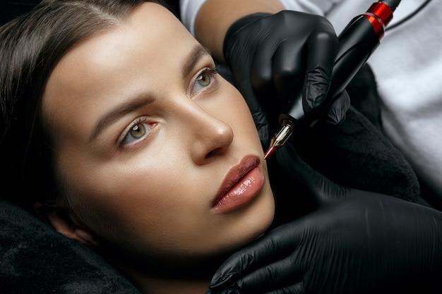美容スタジオで唇の永久的な手順を持っている驚くべきブルネットの女性。上面図