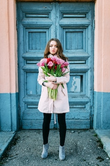 Amazing brunette woman standing in front of old  blue door with a bouquet of tulips.