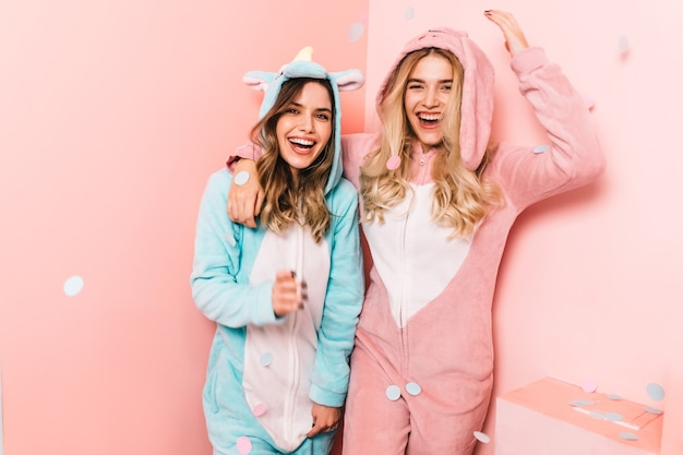 Amazing brunette woman in unicorn costume chilling in weekend with friend