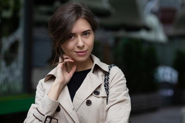 驚くべきブルネットの若い女性が通りを歩きます。