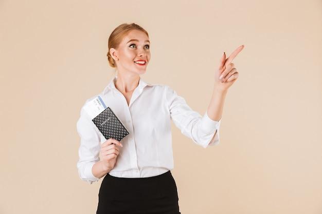 Удивительная деловая женщина, держащая паспорт с билетами. глядя в сторону указывая.