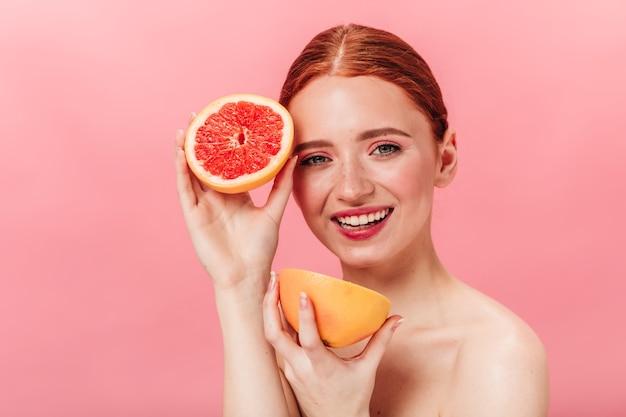 カットグレープフルーツを保持している驚くべき白人の女の子。ピンクの背景にポーズをとる柑橘類と素晴らしい裸の女性のスタジオショット。