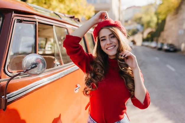 晴れた10月の朝に屋外で時間を過ごす巻き毛の茶色の髪を持つ素晴らしい白人の女の子