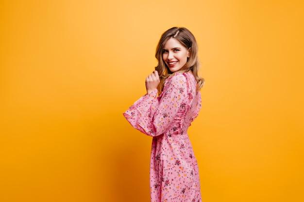 肩越しに見ている長いドレスの驚くべき白人女性。黄色の壁にポーズをとるピンクの衣装でジョクンド巻き毛の女の子。