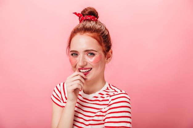 스킨 케어 치료 중 미소로 포즈를 취하는 놀라운 백인 여자. 눈 패치 즐거운 백인 여자의 스튜디오 샷.