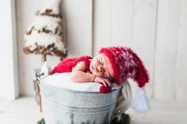 양동이에서 자고 놀라운 매력적인 아기 프리미엄 사진