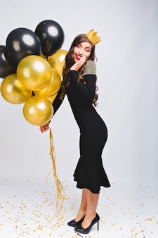 黒いイブニングラグジュアリードレスと新年を祝う頭の上の黄色い王冠、笑顔と黄色と黒の風船、赤い唇、感情を驚かせた顔で驚くほど陽気なスタイリッシュな女性。