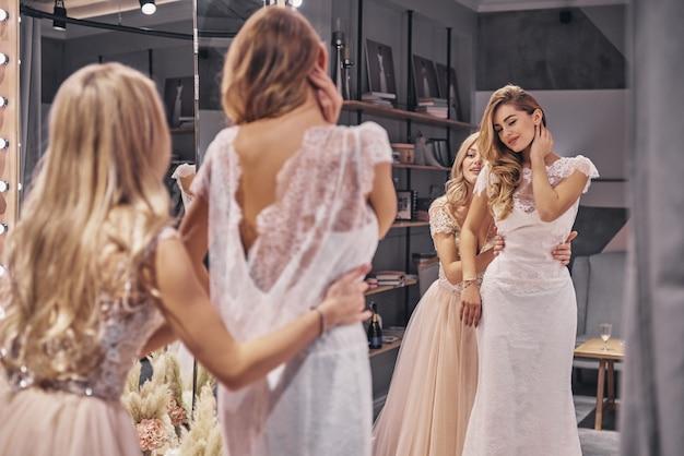 놀라운 선택입니다. 피팅 룸에 서 있는 동안 그녀의 여자 친구에 게 드레스를 조정 하는 매력적인 젊은 여자의 반영