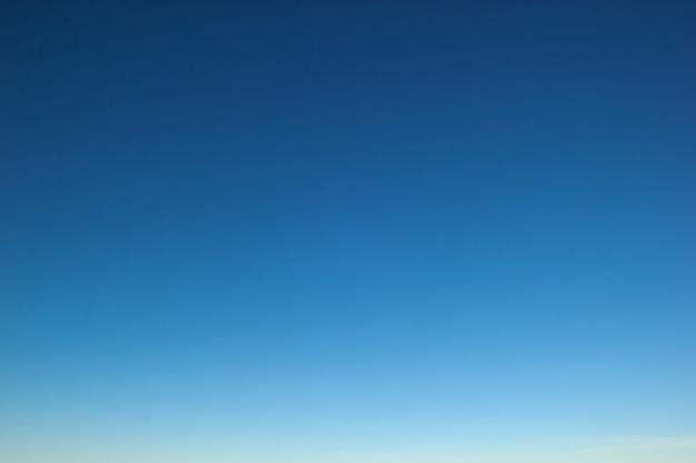 驚くほど澄んだ青い色の夕焼け空のグラデーションの背景。