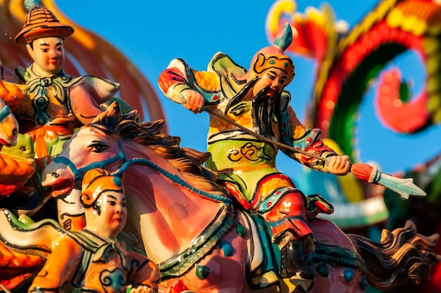 Amazing colorful figurine of the chinese warrior on his horse focused with a spear in his hands