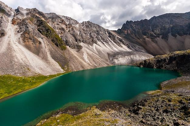 Удивительное красочное озеро с бирюзовой водой рядом со скалами в горах. вокруг много камней. небо затянуто облаками. по горизонтали. Premium Фотографии
