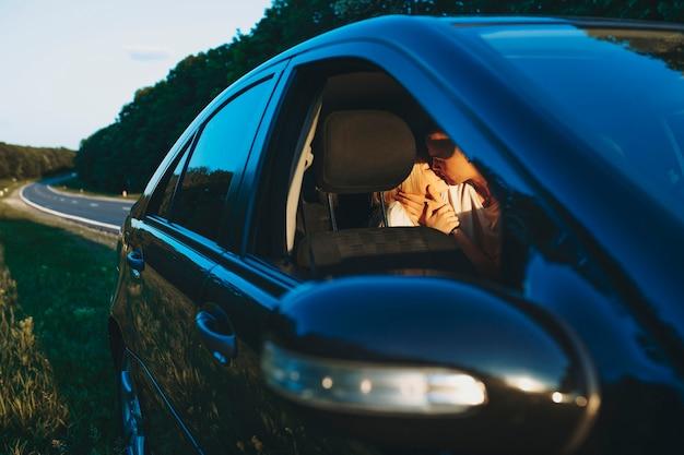 車で旅行中に道路の近くで休んでいる間、車の後ろのベンチでキスしている素晴らしいカップル。