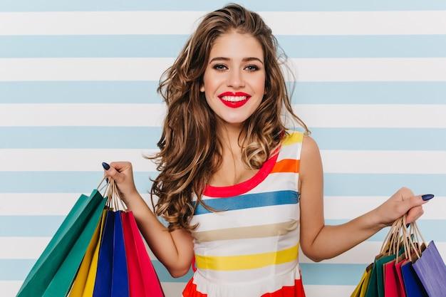 買い物の後に身も凍るような驚くべき巻き毛の女の子。紙袋を持つ至福のヨーロッパの女性の屋内の肖像画。