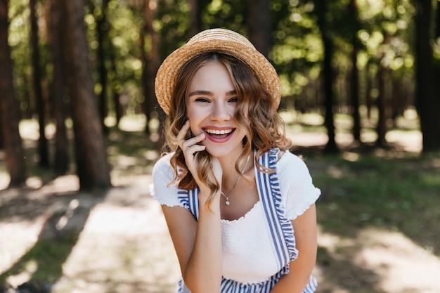 밀 짚 모자 숲에서 시간을 보내는 놀라운 곱슬 소녀. 자연에 포즈 웃는 사랑스러운 여자의 야외 사진.