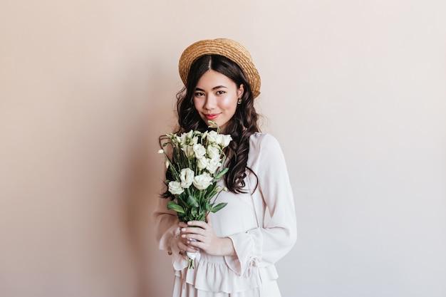 トルコギキョウの花を保持している驚くべき巻き毛の日本人女性。ブーケと恥ずかしがり屋のアジアの女性のスタジオショット。