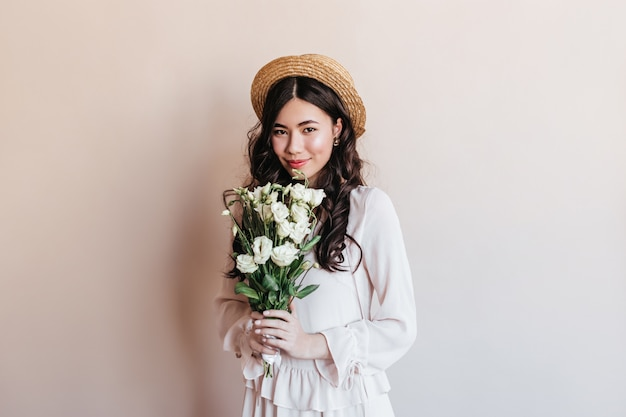 Amazing curly japanese woman holding eustoma flowers. studio shot of shy asian woman with bouquet.