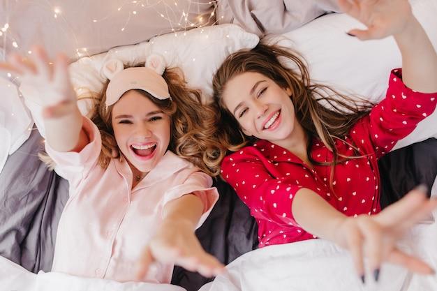 妹と一緒にベッドに横たわっているトレンディなアイマスクの驚くべき巻き毛の女性。寝る前に楽しんでいる2人の女の子のオーバーヘッドの肖像画。