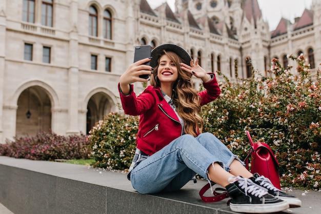 Incredibile donna riccia in scarpe nere che fa selfie davanti all'edificio storico