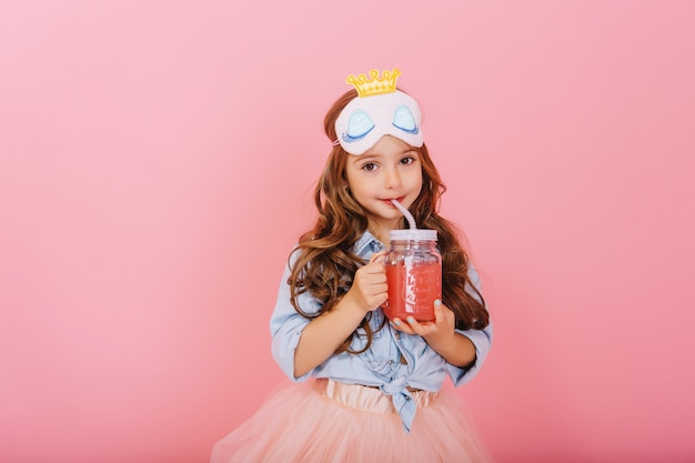 Amazing cute little girl with princess mask on head, long brunette hair drinking juice from glass and looking to camera isolated on pink background. little happiness, expressing true positive emotions