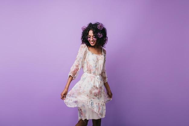 Удивительная темноволосая девушка позирует в модном летнем платье. портрет великолепной африканской женщины, танцующей с вдохновенной улыбкой.