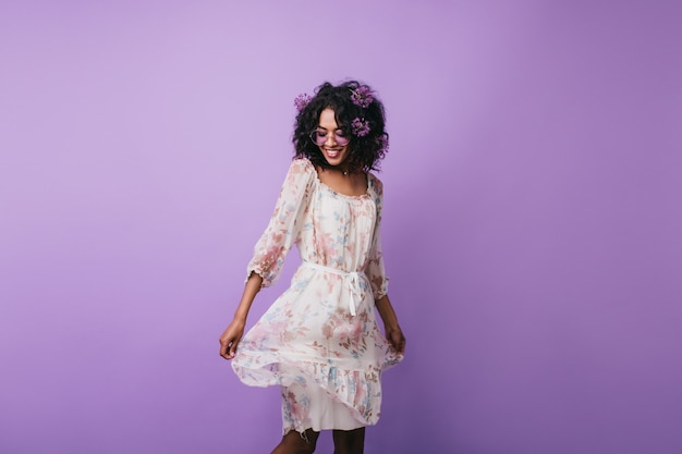 Amazing dark-haired girl posing in trendy summer dress. portrait of gorgeous african woman dancing with inspired smile.