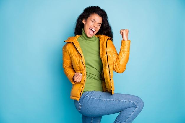 サッカーの試合のゴールを祝う驚くべき暗い肌の巻き毛の女性の悲鳴を上げる着用トレンディな黄色の春のオーバーコートジーンズ緑のプルオーバー孤立した青い色の壁