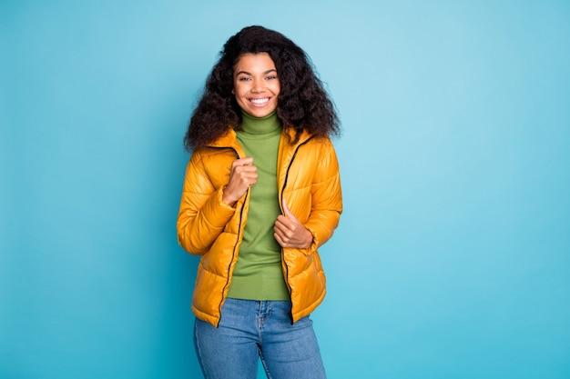 좋은 봄 분위기에서 놀라운 어두운 피부 곱슬 아가씨 산책 착용 유행 노란색 가을 외투 청바지 녹색 풀오버 절연 파란색 벽