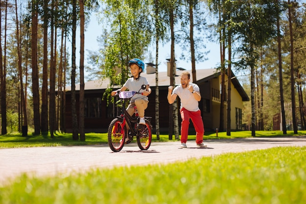 素晴らしい日。笑顔で自転車に乗るように息子に教える愛情深い父親