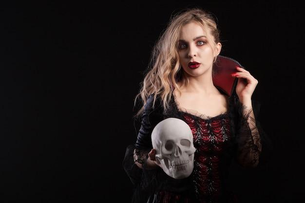 ハロウィーンのカーニバルのために頭蓋骨を持っている吸血鬼のような格好をした驚くべき死んだ女の子。吸血鬼の衣装を着た女性の肖像画。