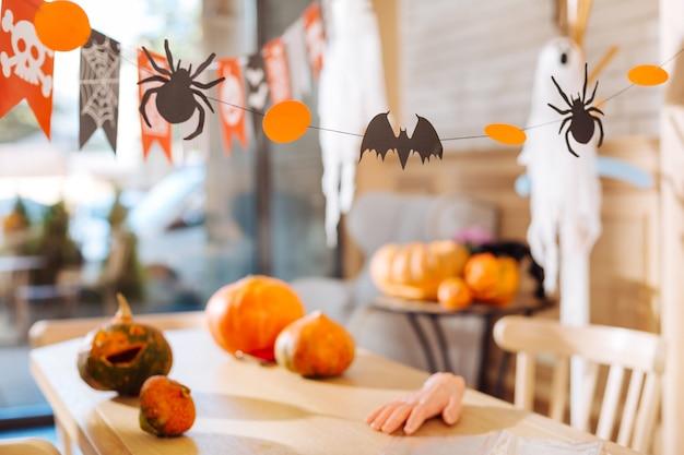 素晴らしい装飾。ハロウィーンのテーブルに横たわっている怖い指の形で描かれたカボチャやお菓子のような素晴らしい装飾