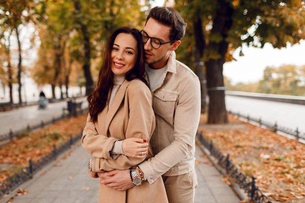 Amazing european couple posing together in cold day. wearing stylish trench. fall season. romantic mood.