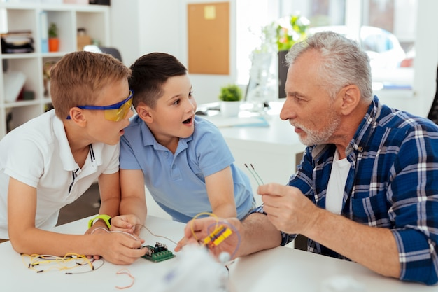 Удивительные факты. любопытные удивленные мальчики смотрят на своего учителя, пораженные новыми знаниями