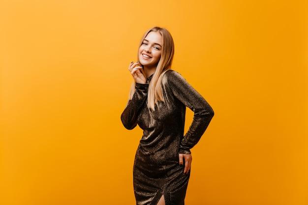 Удивительная светловолосая женщина в элегантном платье улыбается. крытый портрет прекрасной кавказской модели с выражением счастливого лица.