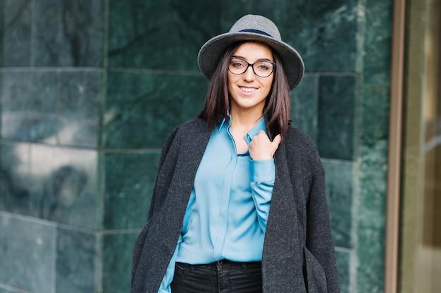 青いシャツを着て素晴らしいファッショナブルな若い女性、グレーのコート、帽子を屋外で街の通りを歩いています。ブルネットの髪、黒いメガネ、笑顔、スタイリッシュな実業家、エレガントな見通し。