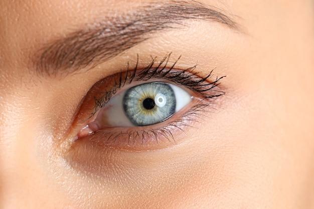 驚くべき女性の青と緑の色の目のクローズアップ