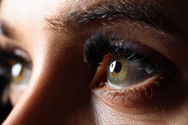 Удивительные женские зеленые глаза с наращенными ресницами крупным планом в технике слабого освещения