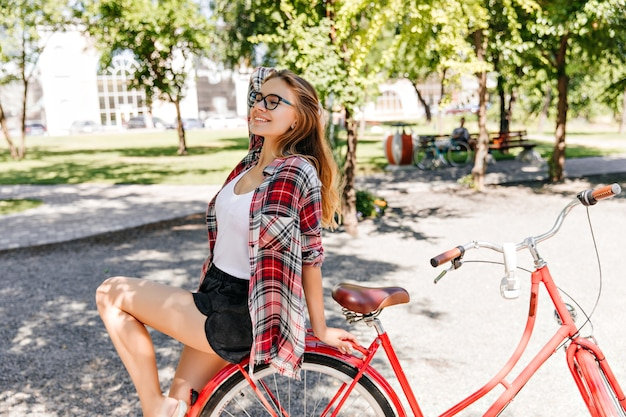 따뜻한 여름날 야외 포즈 안경에 놀라운 여성 모델. 화창한 아침에 자전거에 앉아 관심있는 금발 소녀.