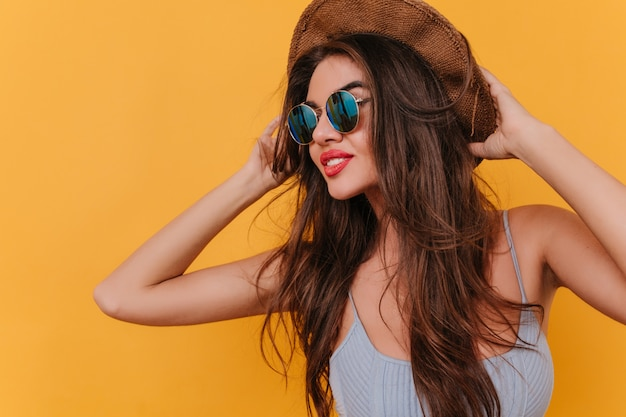 Amazing female model with romantic hairstyle touching her hat and looking away with pensive face expression