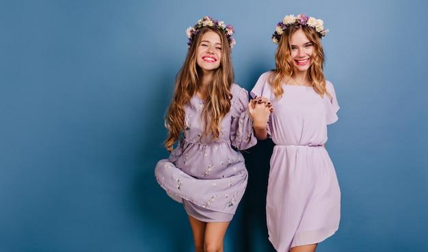Incredibili modelli femminili che tengono le mani con l'espressione del viso felice