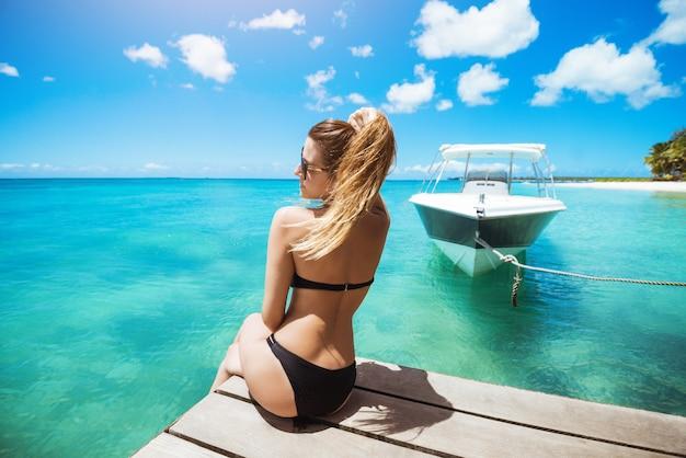 Amazing fit woman in black bikini sunbathing at bright beach